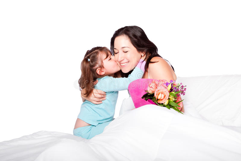El niño da las flores y beso a la mamá en cama foto de archivo libre de regalías