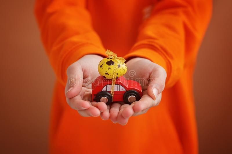 El niño da sostener el huevo de Pascua en el coche en fondo anaranjado Concepto del día de fiesta imagen de archivo libre de regalías