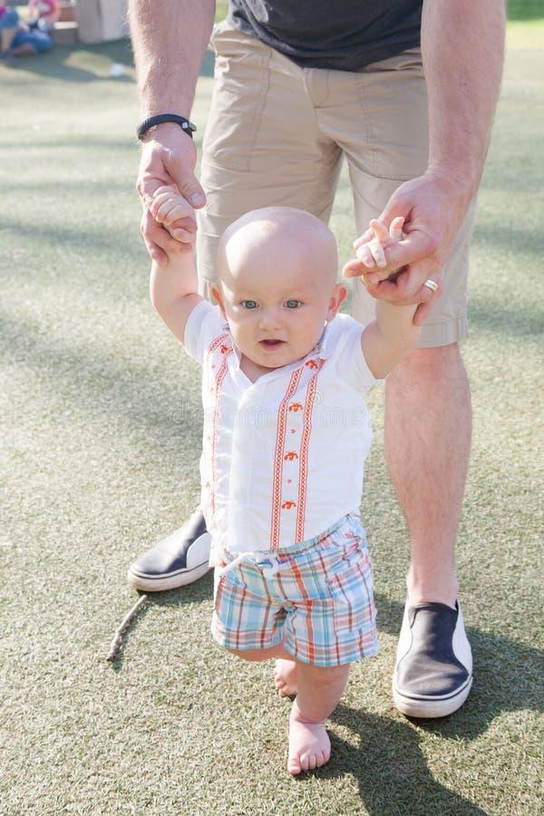 El niño de ayuda del papá aprende caminar imagen de archivo