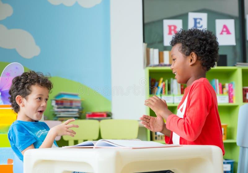 El niño de dos muchachos se sienta en la tabla y el colorante en libro en biblioteca preescolar, concepto de la educación escolar imagen de archivo libre de regalías