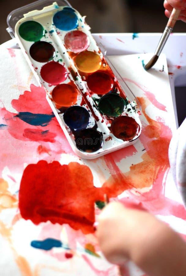 El niño de la foto pinta un cepillo con las pinturas de la miel de la acuarela pequeñas manos en pintura roja fotos de archivo libres de regalías