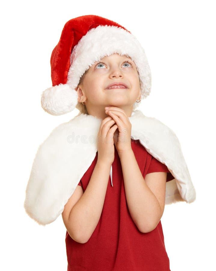 El niño de la muchacha en el sombrero ruega, blanco aislado, concepto de santa del día de fiesta de la Navidad foto de archivo libre de regalías