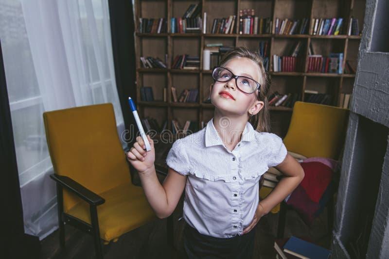 El niño de la muchacha en la biblioteca con los libros en una moda estricta es enga imagen de archivo
