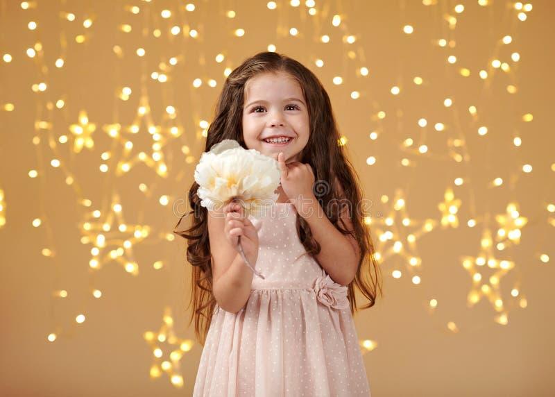 El niño de la muchacha está en las luces de la Navidad, fondo amarillo, vestido rosado fotografía de archivo libre de regalías