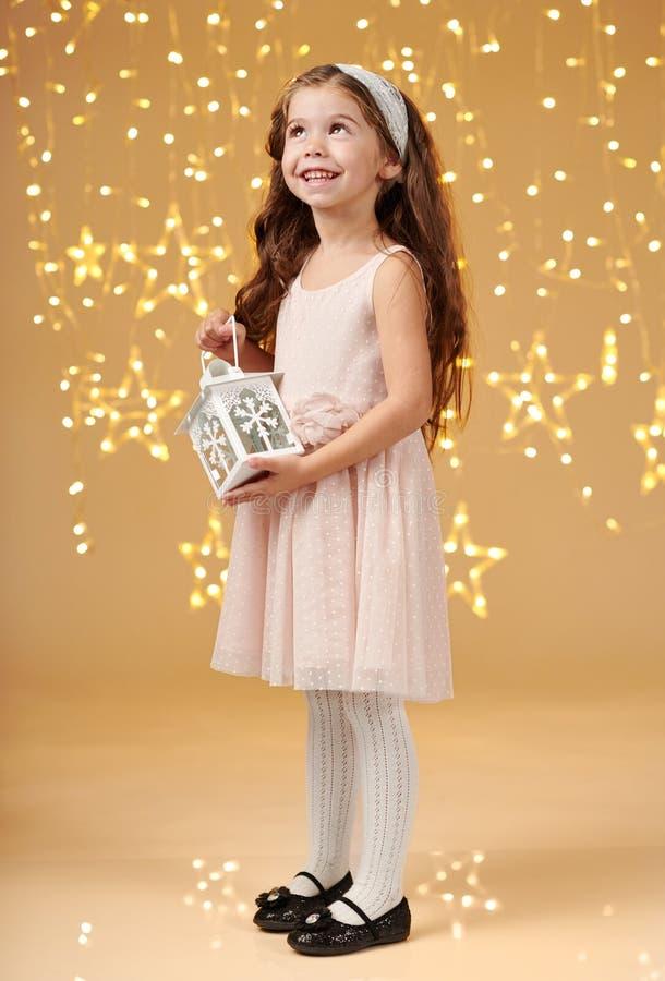 El niño de la muchacha está presentando con la linterna en luces de la Navidad, fondo amarillo, vestido rosado imagen de archivo libre de regalías