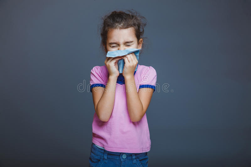 El niño de la muchacha estornuda en el pañuelo en un gris imagenes de archivo