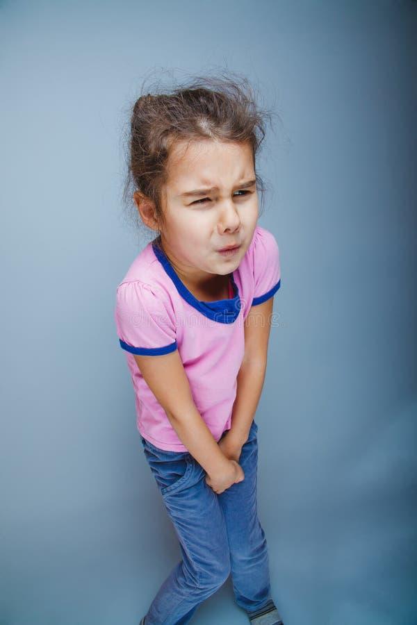 El niño de la muchacha quiere gravemente el retrete en un gris imagen de archivo