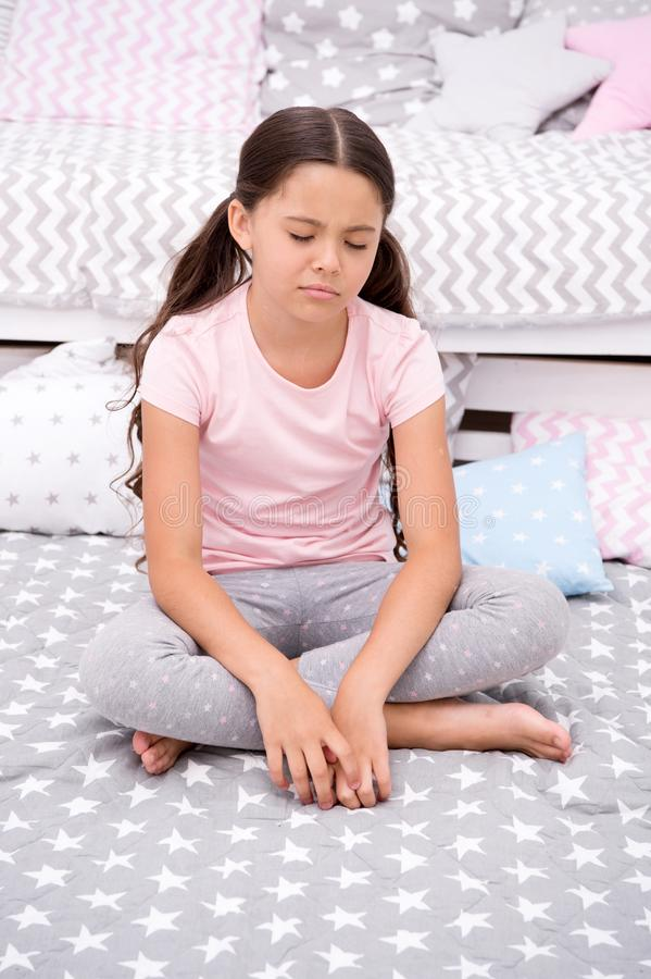 El niño de la muchacha sienta el dormitorio de la cama Embrome infeliz alguien entró en su dormitorio que la molesta Pijamas lind fotografía de archivo libre de regalías