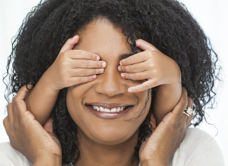 El niño de la mujer del afroamericano con entrega ojos imagen de archivo