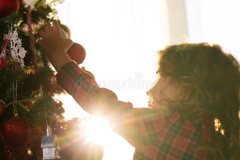 El niño de la niña adorna un árbol de navidad contra la ventana w imagen de archivo