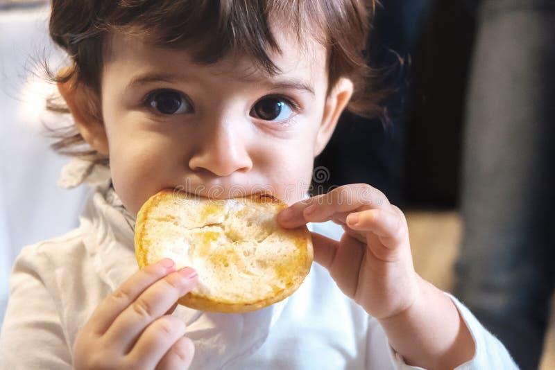 El niño del bebé come la dieta malsana de la consumición de los carbohidratos de la cara del retrato recién nacido del primer par fotografía de archivo libre de regalías