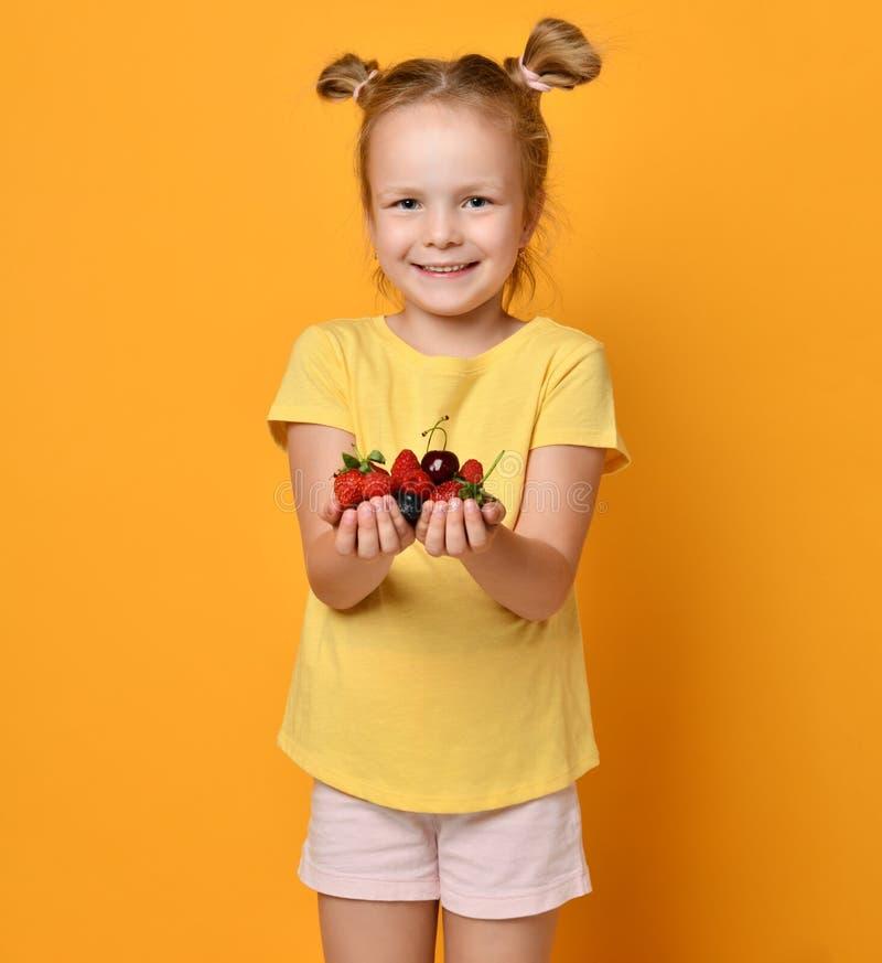El niño del bebé demuestra un puñado de bayas en sus manos y sonrisas de las palmas satisfechas con su cosecha en amarillo fotos de archivo