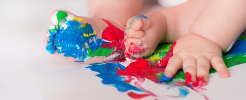 El niño del bebé dibuja con las manos coloreadas de las pinturas, pies sucios Selecti foto de archivo libre de regalías
