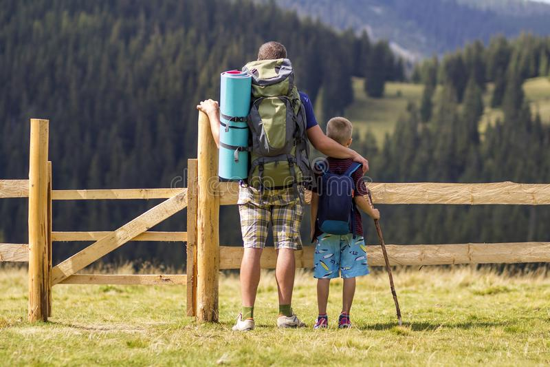 El niño del papá y del hijo con el turista hace excursionismo en la cerca de madera baja en las montañas verdes cubiertas con el  imagen de archivo libre de regalías