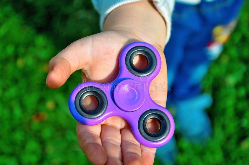 El niño detiene al hilandero en su mano imagen de archivo libre de regalías