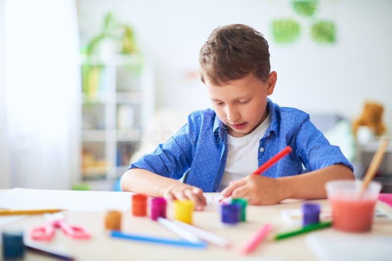 El niño dibuja con una acuarela del cepillo pinta en el papel la letra A foto de archivo libre de regalías