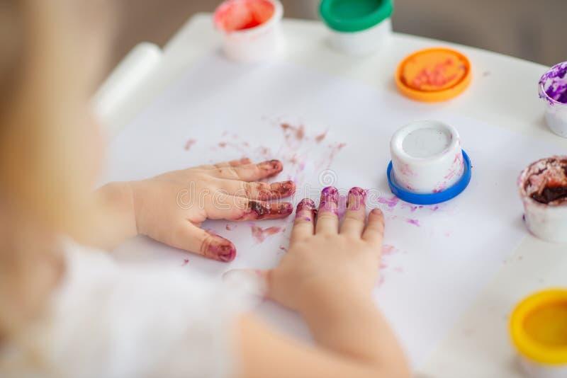 El niño dibuja el primer de las pinturas del finger de la mano en blanco foto de archivo