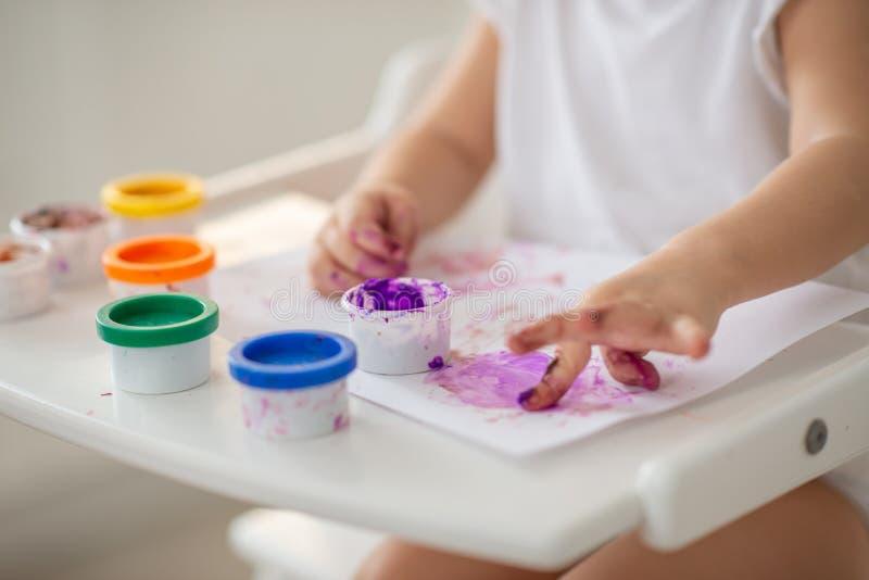 El niño dibuja el primer de las pinturas del finger de la mano en blanco fotografía de archivo