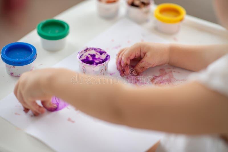 El niño dibuja el primer de las pinturas del finger de la mano en blanco fotografía de archivo libre de regalías