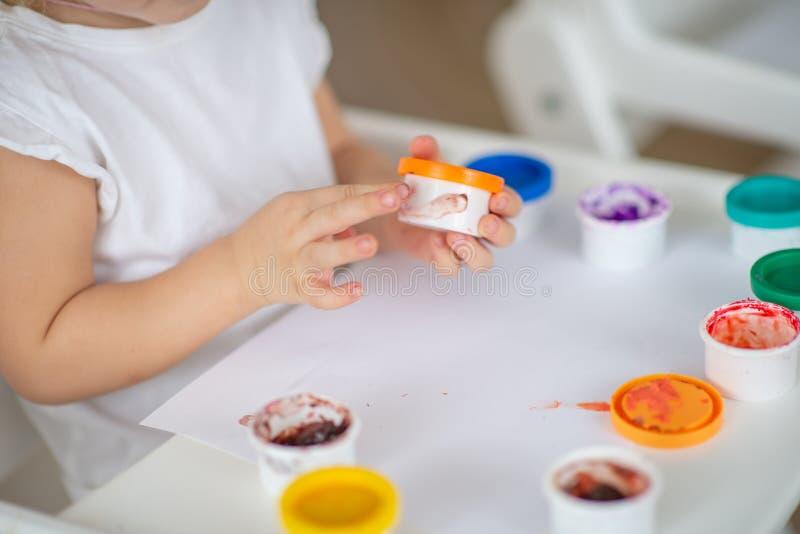 El niño dibuja el primer de las pinturas del finger de la mano en el Libro Blanco fotografía de archivo