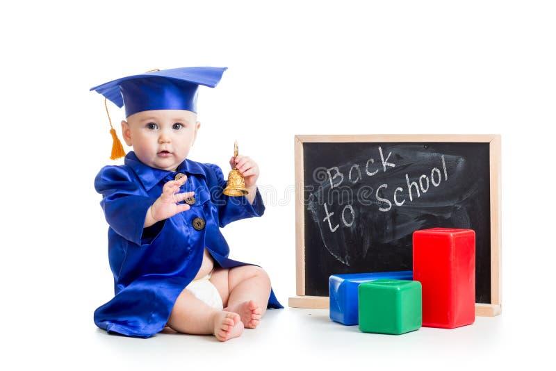 El niño divertido con la campana en académico viste en imagen de archivo libre de regalías