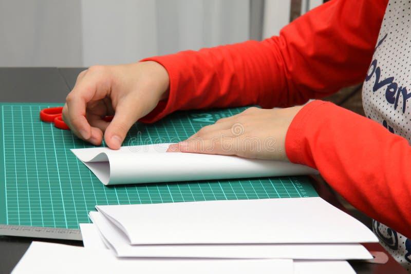 El niño dobla las hojas de papel para hacer un cuaderno fotos de archivo