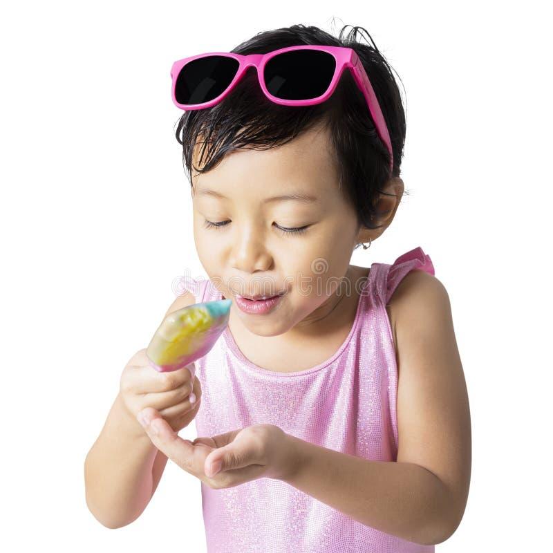 El niño dulce come el helado foto de archivo