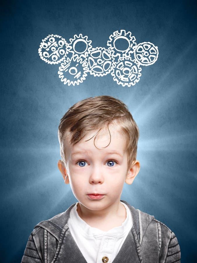 El niño elegante piensa en la mirada de los engranajes foto de archivo