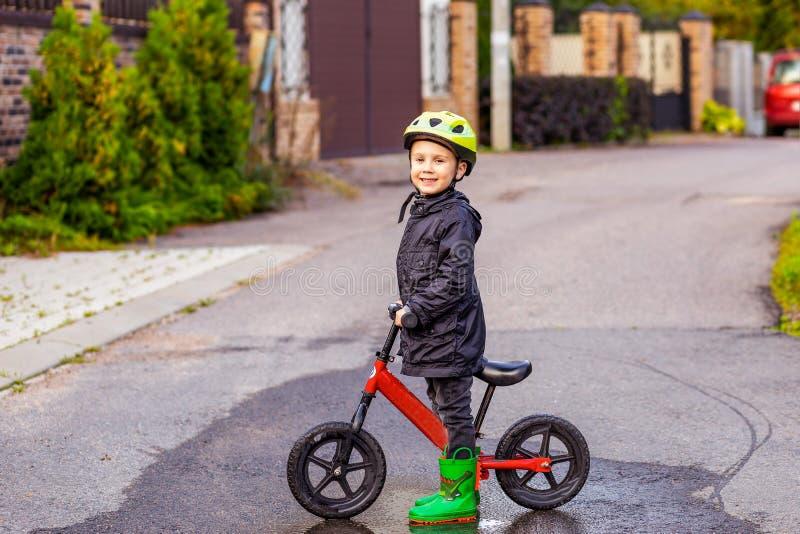 El niño en bici de la balanza del paseo del casco funciona con la bici imágenes de archivo libres de regalías