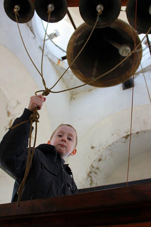 El niño en el campanario imagen de archivo