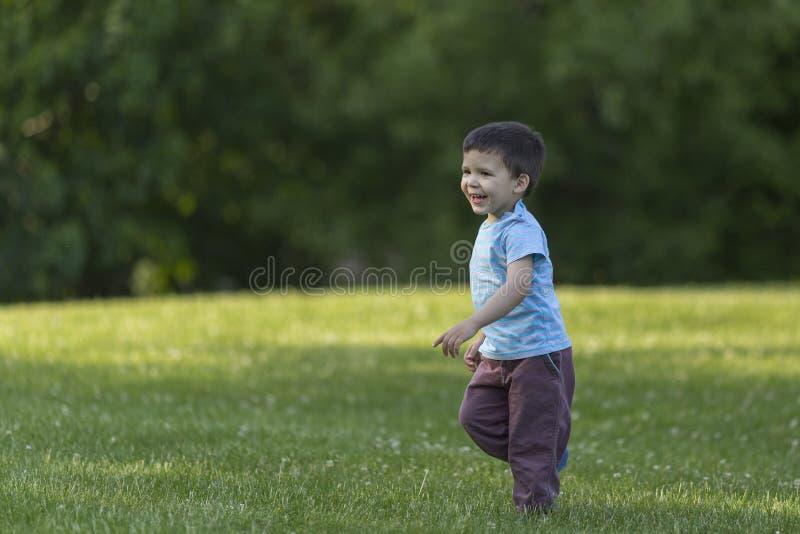 El niño en el funcionamiento y la sonrisa del parque fotos de archivo libres de regalías