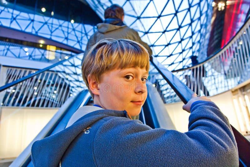 El niño en escalera móvil parece seguro de sí mismo foto de archivo