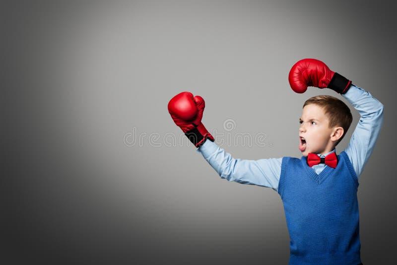 El niño en guantes de boxeo, boxeador elegante del muchacho del niño criado arma para arriba imagen de archivo libre de regalías