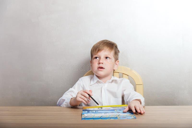 El niño en la camisa blanca dibuja en el colorante imagenes de archivo