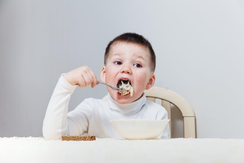El niño en un cuello alto blanco apetitoso come las pastas con una bifurcación en la tabla imagen de archivo libre de regalías