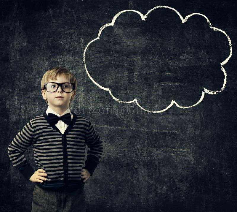 El niño en vidrios piensa la burbuja sobre la pizarra, pensamiento del muchacho del niño foto de archivo