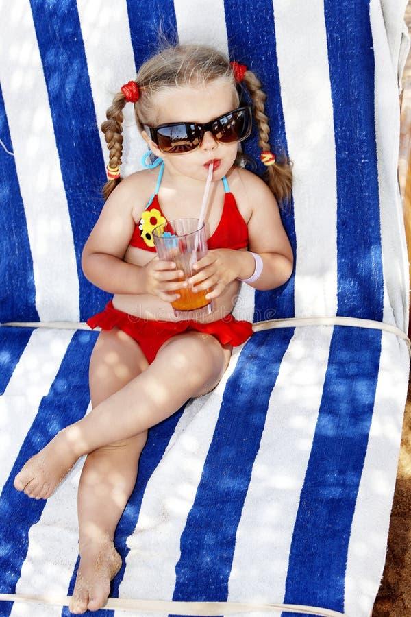 El niño en vidrios y el bikiní rojo beben el jugo. foto de archivo libre de regalías