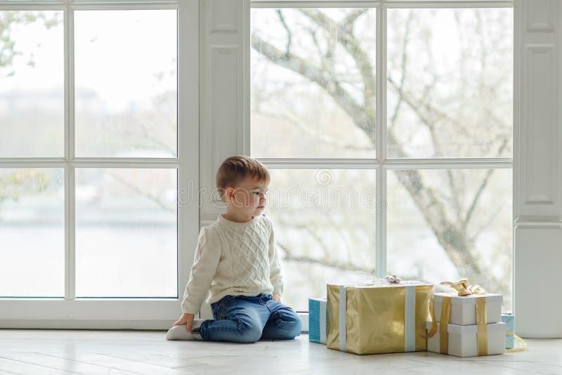 El niño encantador del niño pequeño que se sienta cerca de una ventana grande cerca imagen de archivo
