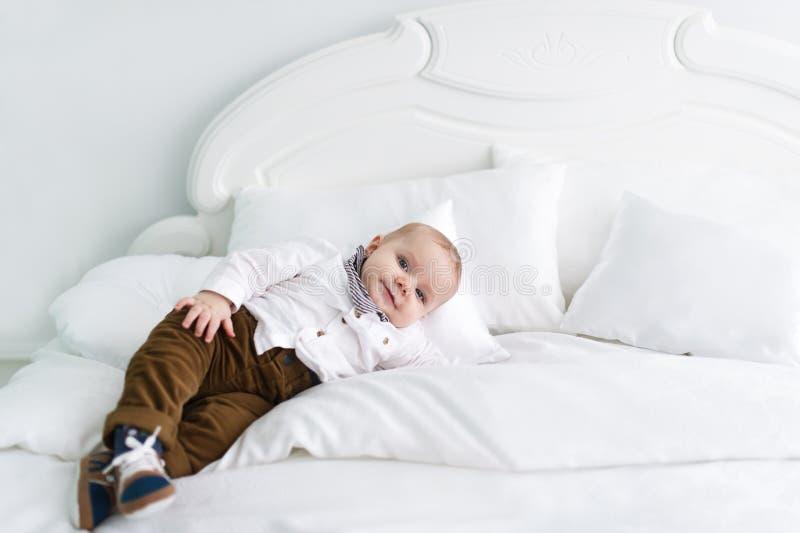 El niño encantador y reservado en ropa miente en la manta blanca en dormitorio foto de archivo libre de regalías