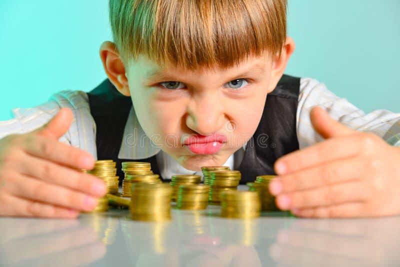 El niño enojado y codicioso sostiene sus monedas del dinero El concepto de avaricia, de avaricia y de vicio de la niñez imagenes de archivo