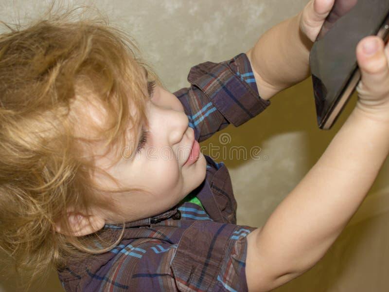 El niño es feliz que a le se permitió jugar con su smartphone de los parent's foto de archivo libre de regalías