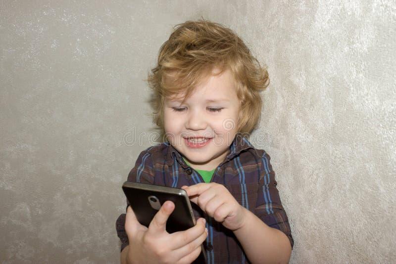 El niño es feliz que a le se permitió jugar con su smartphone de los parent's imagenes de archivo