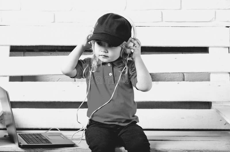 El niño es un amante de la música auricular que lleva del niño cerca del ordenador portátil en el fondo blanco fotos de archivo libres de regalías