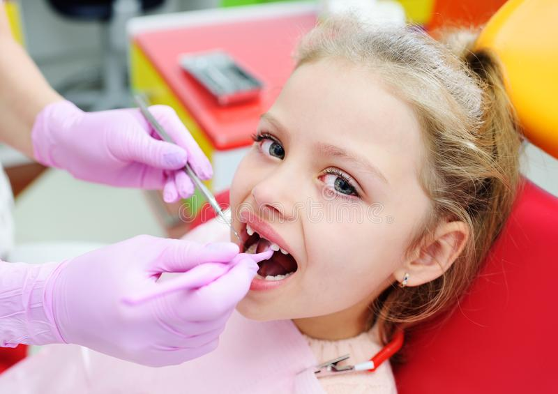 El niño es una niña dulce sin los dientes de leche delanteros en la silla dental El dentista examina los dientes del foto de archivo libre de regalías