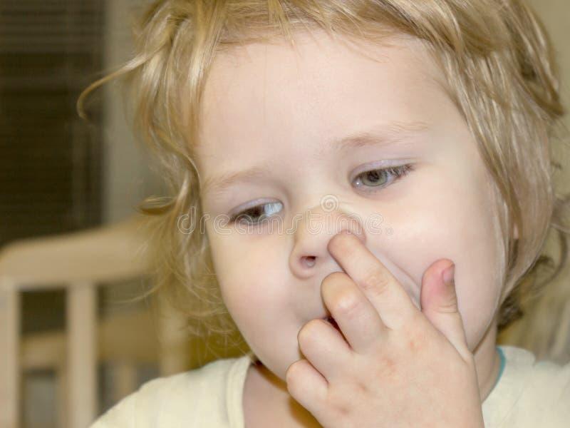 El niño escoge su nariz e intenta conseguir el salpi secado-para arriba de los sinos fotos de archivo libres de regalías