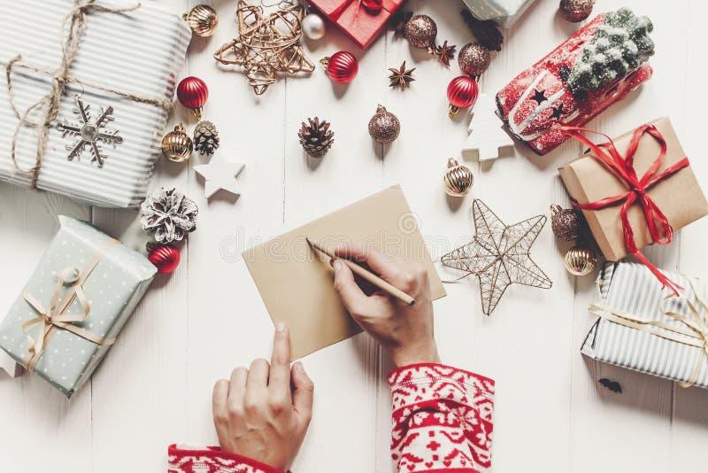 El niño escribe la letra a la opinión superior de Santa Claus manos del niño que llevan a cabo p fotografía de archivo