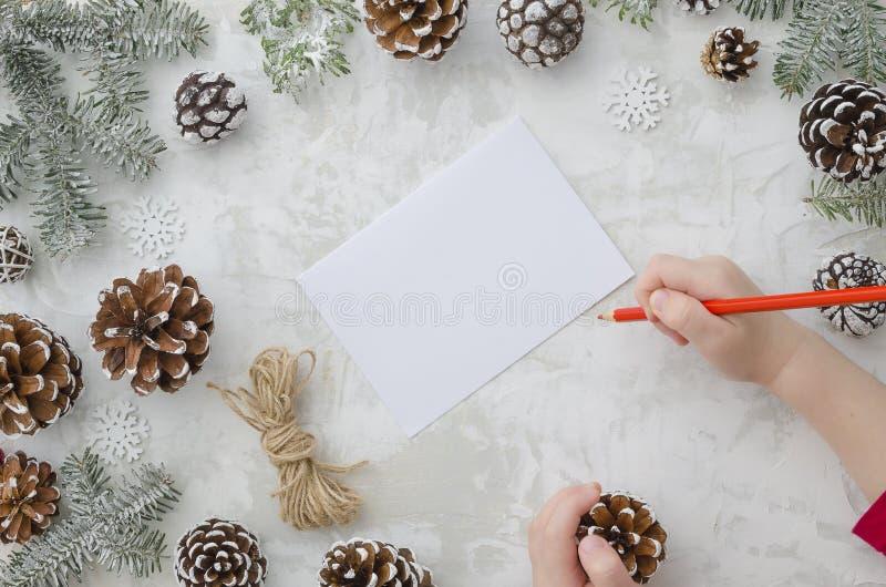 El niño escribe la letra a Santa Claus Las manos del niño, la hoja de papel, lápiz rojo y pino de las decoraciones de la Navidad imágenes de archivo libres de regalías