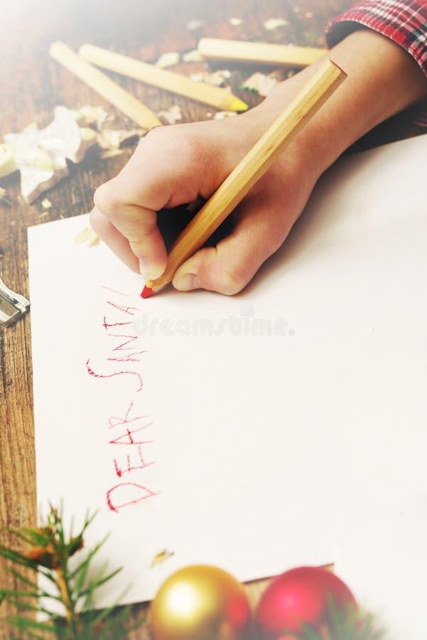 El niño escribe la letra a Santa Claus Manos del ` s del niño, la hoja de papel, lápices y decoraciones de la Navidad foto de archivo