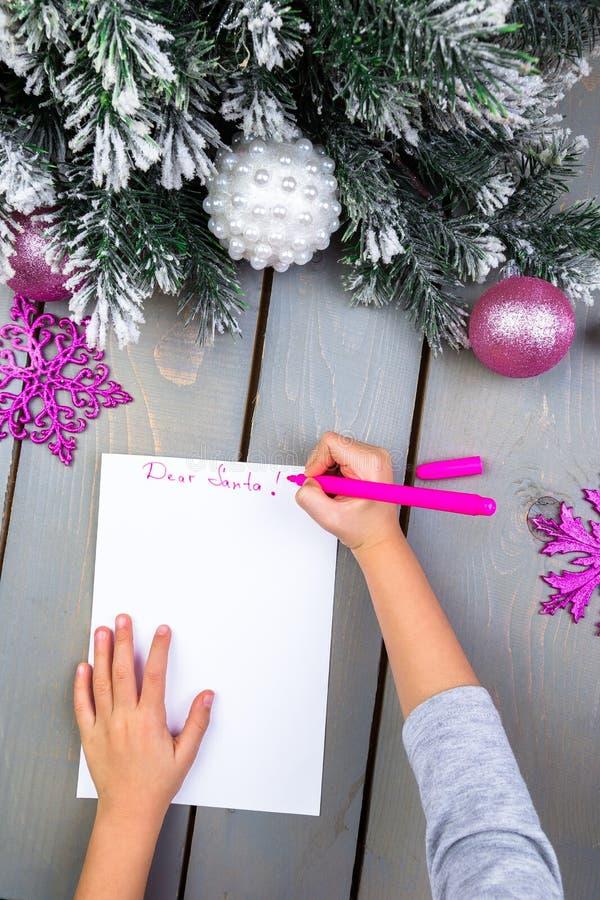 El niño escribe la letra a Santa Claus Manos del niño Visión superior imágenes de archivo libres de regalías