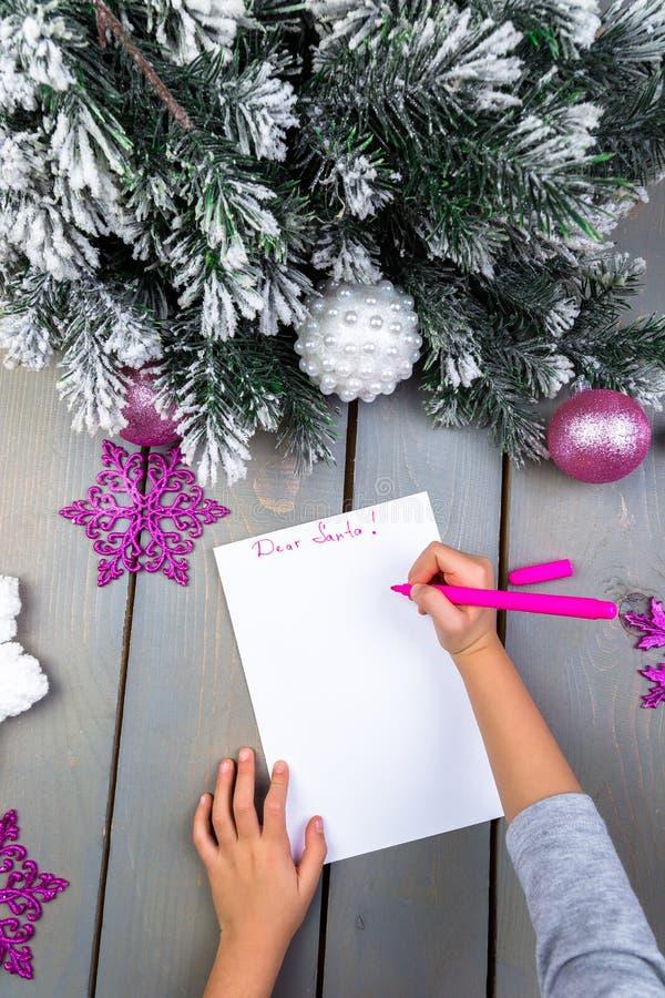 El niño escribe la letra a Santa Claus Manos del niño Visión superior foto de archivo
